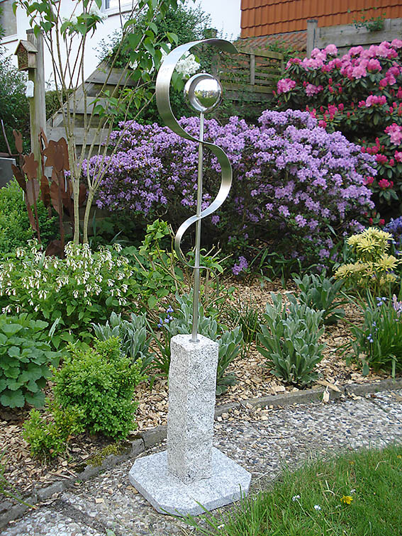 Garten-Kunst-Objekte: Dieser Ästkulapstab steht auf einer Granitplatte.